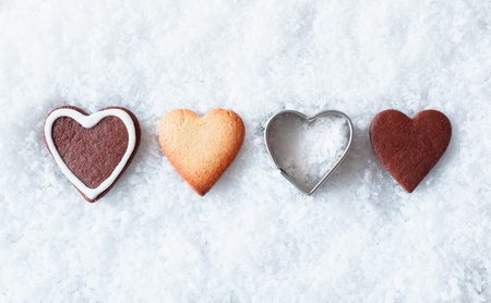 advent time: Romantic Christmas heart cookies with gingerbread and a heart-shaped metal cookie cutter in a line in fresh snow with copyspace above and below for seasonal greetings Stock Photo