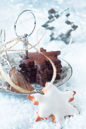 christmass: Delicious freshly baked Christmas star cookies with white and chocolate icing served on a dish in snow with a decorative ribbon