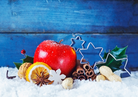 Colourful Christmas still life background wit a ripe red apple, spices, nuts and metal stars nestled in snow in front of blue wooden boards with copyspace photo
