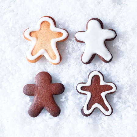 Tasty Christmas gingerbread men cookies with decorative icing lying on a bed of snow with copyspace photo