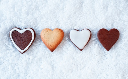 Row of crisp baked gingerbread hearts on a snowy background with copyspace above and below for Christmas greetings photo