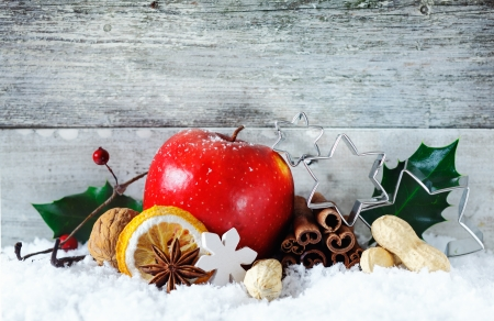 advent: Een heerlijke rijpe rode verse appel met kaneel kruiden en noten in een besneeuwde Kerst achtergrond tegen grijze houten planken met copyspace