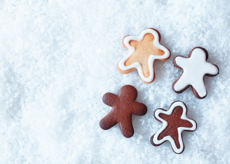 A variety of decorative Christmas gingerbread men on snow wth copyspace for seasonal greetings photo