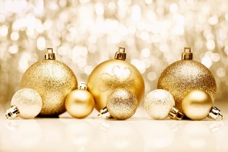 Un arreglo de oro adornos de Navidad contra un bokeh festivo de luces parpadeantes de oro con copyspace