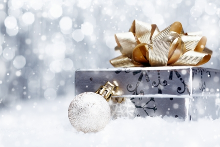 Silver Christmas gift with a huge ornamental golden bow lying with a bauble on a bed of fresh snow with falling snowflakes and copyspace