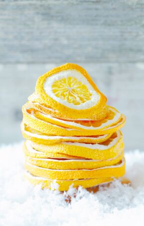 Stack of colourful dried orange slices to season warm winter drinks and refreshments on a bed of snow with copyspace Stock Photo - 15213878