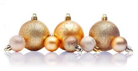 A line of large and small gold Christmas baubles with reflections against a white background Stock Photo - 15213885