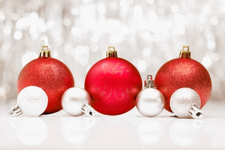 Background of red Christmas baubles with a bokeh of sparkling festive party lights and copyspace for your seasonal greetings