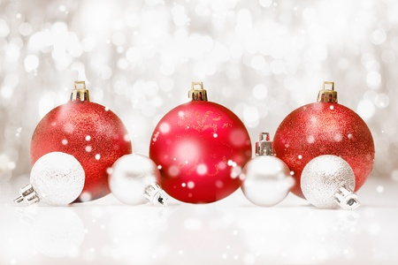 seasonal greetings: Background of red Christmas baubles in falling snow with bokeh and copyspace for your seasonal greetings Stock Photo