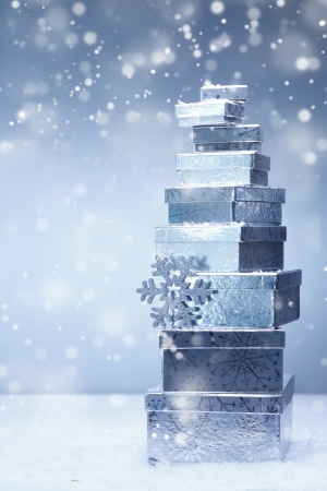 A stacked tower of silver Christmas gifts in diminishing sizes and different angles in falling snow with copyspace photo