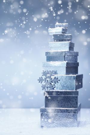 noel argent�: Une tour de cadeaux de No�l empil�s argent dans les tailles diminuent et les diff�rents angles de la neige qui tombe avec copyspace Banque d'images
