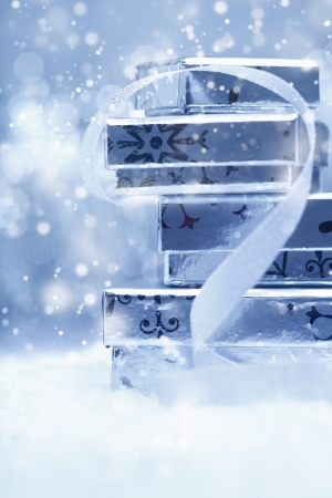 Ethereal festive background with a stack of silver Christmas gift boxes with a decorative ribbon in falling snow photo