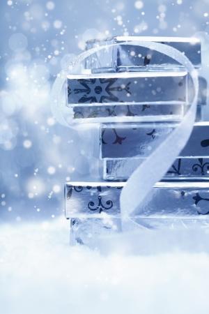 noel argent�: Ethereal fond de f�te avec une pile de bo�tes en argent cadeau de No�l avec un ruban d�coratif dans la neige tombante Banque d'images