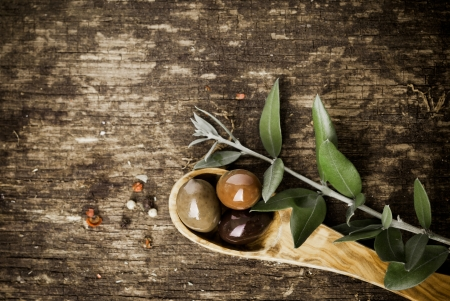 Fresh olives in a wooden spoon on a grungy textured rustic wood table with copyspace photo