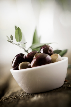 tilted view: Tilted view of a bowl of fresh black olives with shallow dof and copyspace