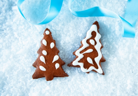 Crisp brown gingerbread Christmas trees with decorative icing lying on snow with a festive blue ribbon photo