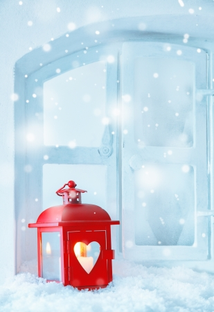 Red Christmas lantern guiding light with a glowing burning candle on a windowsill in falling snow with copyspace for your seasonal greetings photo