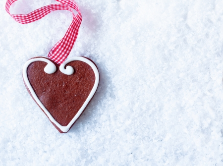 Gingerbread heart with decorative icing and a festive red and white checkered ribbon on snow with copyspace for your Christmas or Valentine greetings photo