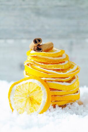 A stack of dried orange slices and cinnamon on snow for seasoning your hot drinks and dessert during a cold winter Stock Photo - 15213921