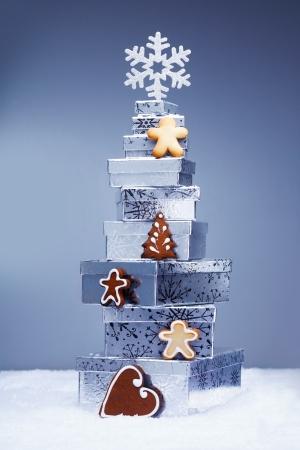 cajas navide�as: Pila de tonos fr�os regalos de Navidad en la nieve con crujiente de galletas de jengibre y un copo de nieve que representa la temporada de invierno Foto de archivo