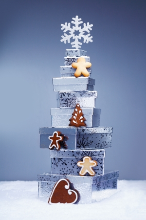 Stack of cool toned Christmas gifts in snow with crunchy gingerbread cookies and a snowflake depicting the winter season photo