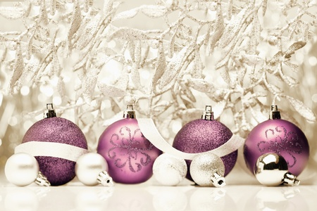 seasonal greetings: Decorative purple Christmas balls with ribbon on a vintage gold background of fabric and foliage with copyspace for your seasonal greetings