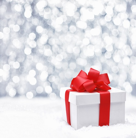atmosphere: Decorative white gift box with a large red bow standing in fresh snow against a background bokeh of twinkling party lights