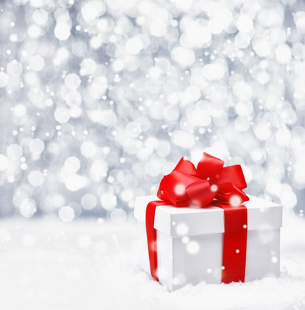 Festive Christmas gift with a large ornamental red ribbon and bow in falling snow with a bokeh and copyspace Stock Photo - 15213930