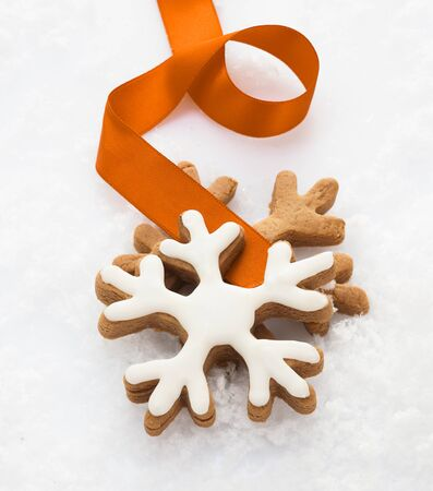 twirled: Decorative iced snowflake biscuits with a twirled gold ribbon lying on a bed of fresh white snow conceptual of winter and the Christmas season Stock Photo