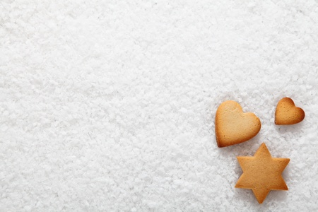 seasonal greetings: Freshly baked hearts and star Christmas cookies on a background of natural fresh snow with copyspace for your seasonal greetings