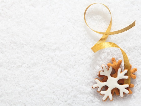 twirled: Decorative Christmas biscuit ornament in the form of an iced snowflake with a twirled gold ribbon lying on a bed of fresh white snow with copyspace for your text