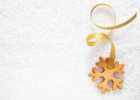 christmass: Crisp fresh Christmas snowflake biscuit with a decorative gold ribbon on a background of fresh snow with copyspace for your greetings Stock Photo