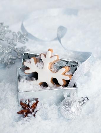 weihnachtskuchen: Weihnachten iced snowflake Keks in einer Geschenk-Box liegend im Schnee durch andere festliche Verzierungen umgeben und Sternanis würzen