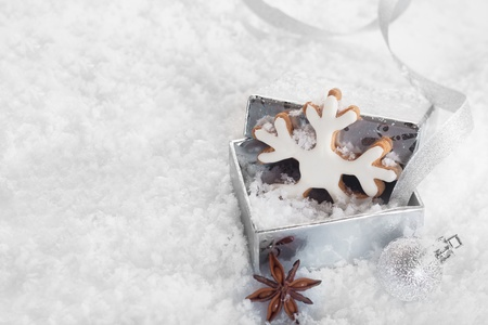 christmass: Christmas Cookie in a silver gift box on snowy background with copyspace