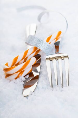 Silver knife and fork with festive striped candy canes on snow for a decorative Christmas table setting photo