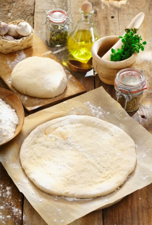 Preparing homemade Italian pizza with a newly rolled dough base surrounded by ingredients for the topping photo