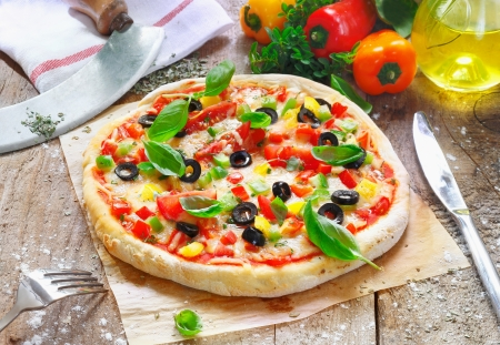 pizza oven: Freshly cooked vegetarian pizza served on oven paper in the kitchen surrounded by various ingredients used in the preparation Stock Photo