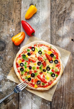 overhead: Overhead view of a delicious colourful homebaked pizza with a thick golden crust and topped with cheese, peppers, tomatoes and olives Stock Photo