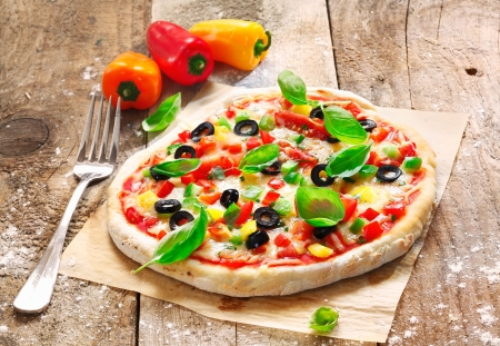pizza: Delicious freshly cooked homemade vegetarian Italian pizza topped with cheese, vegetables and fresh herbs and served on an old wooden surface