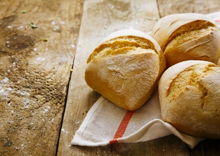 crusty: Crisp freshly baked crusty rolls on a napkin on old rustic wooden boards Stock Photo
