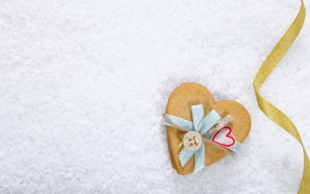 Snow background with a decorated heart shaped cookie and festive ribbon with copyspace for your Valentines or Christmas greeting photo