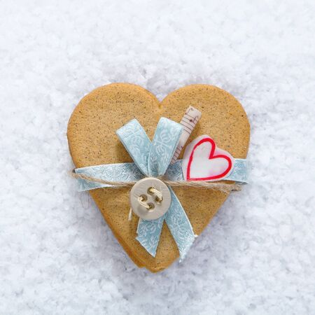 wintry: Decorative biscuit heart with bow and button on a bed of snow for your Valentines or Christmas holiday wishes