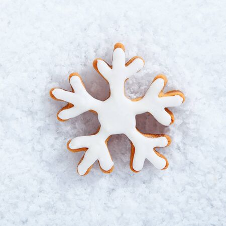 christmass: Iced snowflake biscuit on snow for your winter theme or seasonal Christmas greetings