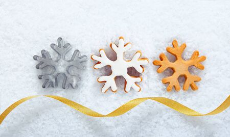 seasonal greeting: Christmas cookies in the shape of ornate snowflakes lying in a line on snow with a decorative gold ribbon for your seasonal greeting