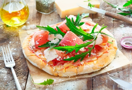 Preparing a tasty pizza in the kitchen using a crisp base topped with fresh herbs, ham, rucola, cheese and tomato photo