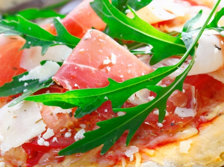 Closeup of delicious fresh ingredients used as a topping for Italian pizza with thinly sliced ham, tomato, fresh herbs,rucola and cheese