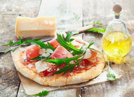 thinly: Preparing homemade ham pizza with fresh ingredients including thinly sliced ham, cheese, herbs and tomato