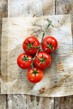 Bunch of fresh red tomatoes in grungy kitchen on a piece of stained, wrinkled oily oven paper on an old wooden tabletop photo