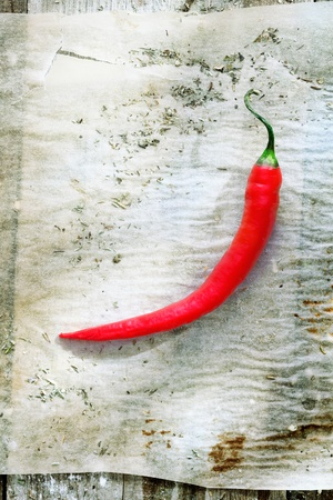 soiled: Single hot chili on grungy soiled paper in a kitchen on a rustic wooden table