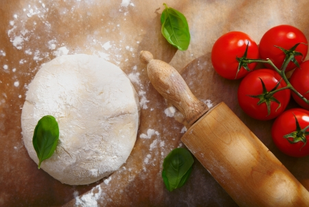 homemade style: Ingredients for homemade pizza with a pile of bread dough for the base left to rise alongside fresh ripe red tomatoes and basil with a wooden rolling pin